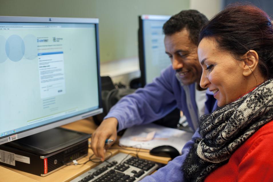 Två elever samarbetar vid en dator.