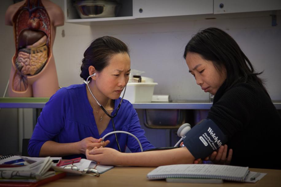 En elev mäter blodtrycket på en annan elev i ett klassrum.