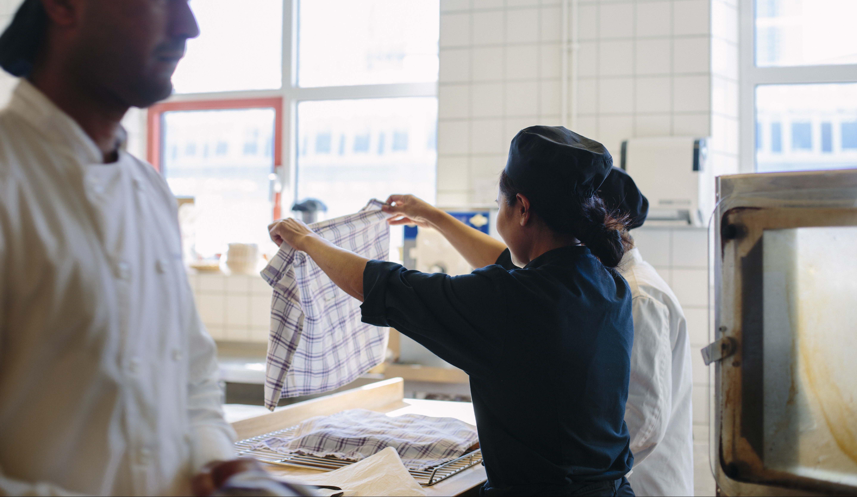 kvinna lyfter på bakduk i restaurangkök