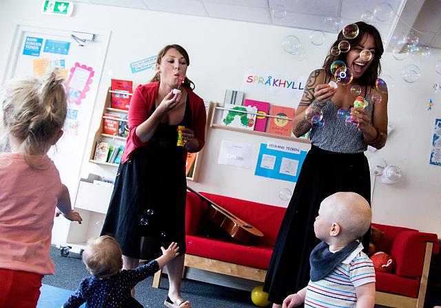 Två vuxna kvinnor blåser såpbubblor till små barn